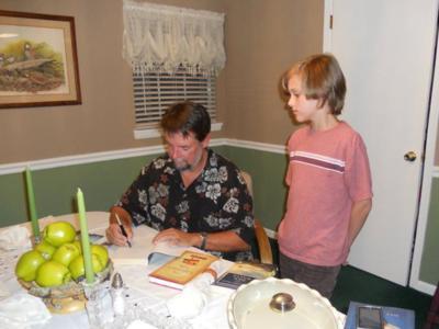 dan-signing-book-for-teen-at-perry-book-club-june-2011_400x300